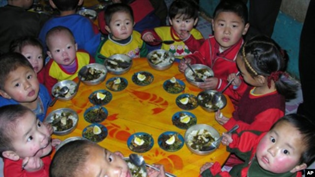 In this photo released by the World Food Program, North Korean children eat a lunch, including rice provided by the U.N. World Food Program.