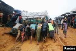Rohingya refugees pushing a truck that is stuck in mud after heavy rain at Kutupalong camp in Cox's Bazar, Bangladesh, July 4, 2018.