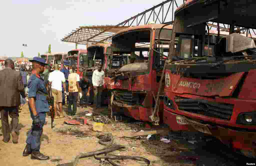 Bomb experts search for evidence in front of buses at a bomb blast scene in Abuja, April 14, 2014.