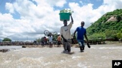 FILE - People cross a river with their belongings where a bridge once stood in Phaloni, Southern Malawi, Jan 22, 2015.