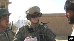 Army 1st Lieutenant Sean Mahard (C) talks with Afghans in Logar province