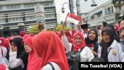 """Berbagai kelompok agama memeriahkan parade """"Bandung Rumah Bersama"""" yang digelar Sabtu, 15 Februari 2020. Nampak kelompok muslimah berkerudung dengan tema merah putih membawa bendera. (Foto: RIo Tuasikal/VOA)"""