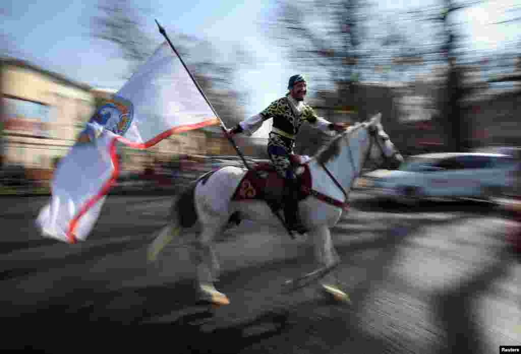 A reveler rides a horse as he holds a city flag during a parade as part of Nowruz, an ancient holiday marking the spring equinox, in Almaty, Kazakhstan.