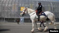 FILE - A French policeman patrols on a horse during a mock chemical attack drill at the Pierre Mauroy stadium in Villeneuve d'Ascq, France, April 21, 2016, in preparation of security measures for the 2016 European soccer championship.