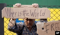 """Một người đàn ông đứng bên ngoài hàng rào đoàn tàu bị dừng lại với biểu ngữ """"Thế giới ở đâu"""" ở thành phố Bicske, Hungary, ngày 4 tháng 9, 2015."""