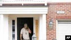 یکی از ماموران امنیتی در مقابل منزل این پلیس در ویرجینیای آمریکا.