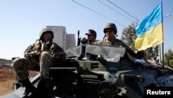 9月5日在南部港口城市马利乌波尔的一个检查哨卡,乌克兰军人坐在一辆装甲运兵车上。