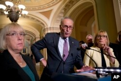 FILE - Senate Minority Leader Sen. Chuck Schumer of N.Y., accompanied by Sen. Patty Murray, D-Wash., left, and Sen. Maggie Hassan, D-N.H., right, speaks to reporters as Senate Republicans faced defeat on the Graham-Cassidy bill, the GOP's latest attempt to repeal the Obama health care law, at the Capitol in Washington, Sept. 26, 2017.