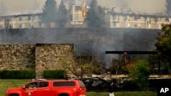 Kebakaran hutan di California juga menghantam hotel Hilton di Santa Rosa, Senin, 9 Oktober 2017. Kebakaran hutan yang diperparah dengan hembusan angin kencang yang menyapu California Utara, memaksa penduduk setempat untuk segera pindah ke lokasi yang lebih aman melalui asap dan api saat kebakaran juga ikut menghanguskan rumah-rumah di sekitarnya. (AP Photo / Ben Margot)