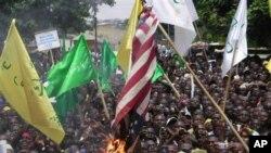 Warga yang marah atas video anti Islam membakar bendera AS di kota Kaduna, Nigeria dalam demonstrasi hari Senin (24/9).