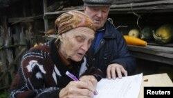 Belaruslik ayol saylov varaqasini to'ldirmoqda. 23-sentabr, 2012-yil.