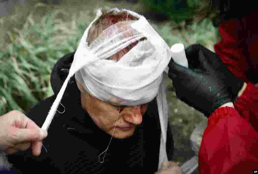 Люди надають медичну допомогу пораненому протестувальнику