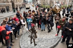 A crowd gathers around a statue of a fearless girl facing the Wall Street Bull, Wednesday, March 8, 2017, in New York.