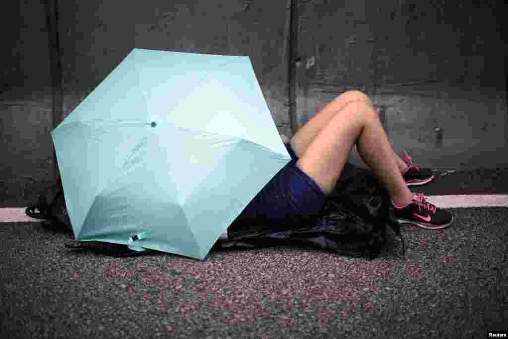 A protester sleeps under an umbrella on a street outside the government headquarters in Hong Kong, Oct. 2, 2014.