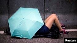 Người biểu tình ngủ cạnh cây dù trên đường phố gần trụ sở chính phủ ở Hong Kong.