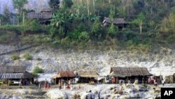 Karen villagers do their routines on the bank of the Salween river