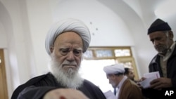 An Iranian clergyman casts his ballot at a polling station at Massoumeh shrine in the holy city of Qom, 130 kms south of Tehran, during parliamentary elections on March 2, 2012.