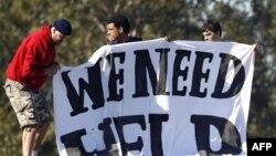 Những người trong trung tâm tạm giữ ở Villawood, Syney cầm một biểu ngữ phản đối với hàng chữ 'Chúng tôi cần được giúp đỡ'
