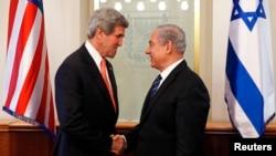ລັດຖະມົນຕີການຕ່າງປະເທດສະຫະລັດ ທ່ານ Kerry (ຊ້າຍ) ຈັບມືກັບ ທ່ານ Benjamin Netanyahu (ຂວາ).
