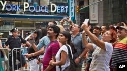 Para pengunjung berfoto selfie di depan layar raksasa di Times Square kota New York tahun lalu (foto: dok).