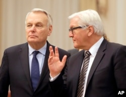 German Foreign Minister Frank-Walter Steinmeier, right, and French Foreign Minister Jean-Marc Ayrault talk ahead of their meeting with Ukrainian officials in Kiev, Feb. 22, 2016. Germany and France are pushing for Ukraine to move ahead with reforms needed in order to implement the year-old Minsk peace agreement.