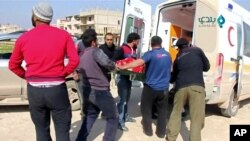 FILE - An injured person is carried on stretcher into an ambulance after an airstrike on location targeted by government and aliied forces, in Khan Sheikhoun, Idlib, Syria, Feb. 26, 2019,