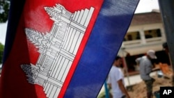 FILE: In this Saturday, July 17, 2010 photo, a Cambodian flag with a depiction of Angkor Wat in the center is hoisted near a construction site in Siem Reap, about 143 miles (230 kilometers) northwest of the capital, Phnom Penh, Cambodia.