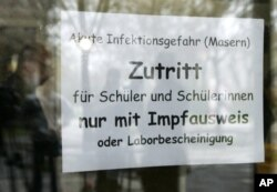FILE - A sign at the entrance of a school in Freiburg, southern Germany, April 11, 2008, advises that only vaccinated children are allowed to enter.