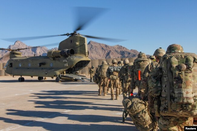 FILE - Soldiers attached to the 101st Resolute Support Sustainment Brigade, Iowa National Guard and 10th Mountain, 2-14 Infantry Battalion load onto a Chinook helicopter to head out on a mission in Afghanistan, Jan. 15, 2019.