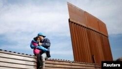 Migran Peyi Ondiras ki t ap vole sou yon kloti pou yo te ka kite Meksik epi antre Ozetazini, nan zòn Tijuana, Meksik (Foto: REUTERS/Mohammed Salem/Dat: 12 desanm 2018).