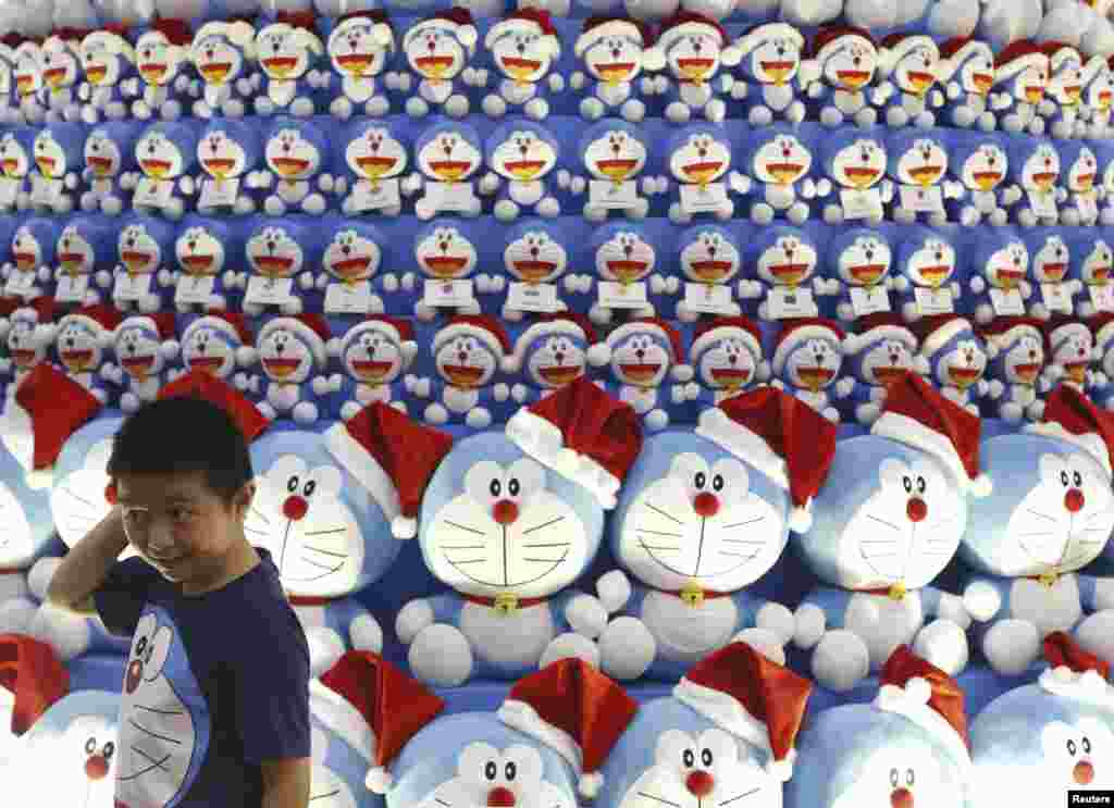 A boy wearing a Doraemon t-shirt stands in front of a Christmas tree made up of Japanese Manga character Doraemon at a shopping mall in the central business district in Singapore.