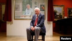 FILE - David Attenborough poses next to a portrait of himself by Bryan Organ to mark his 90th birthday at New Walk Museum and Art Gallery in Leicester, Britain, Sept. 22, 2016.