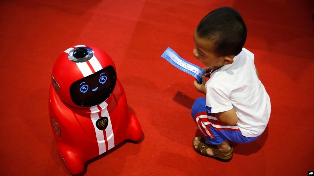 Một em bé cầm vé vào cửa ngồi nhìn môt robot tự học tinh khôn tại Hội nghị Robot Thế giới 2017 ở Bắc Kinh, ngày 23/8/2017.