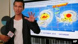 """马尼拉东北部的奎松市一名气象预报人员在记者会上向媒体解释台风""""巨爵""""可能来袭(2015年10月16日)"""