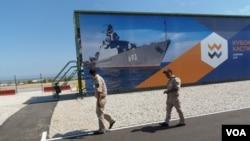 哈萨克斯坦同中国和俄罗斯到保持很好关系。2015年俄罗斯在里海岸边举行的一次军事比赛活动上,两名哈萨克军官走过。中国也参加了那次比赛。(美国之音白桦拍摄)