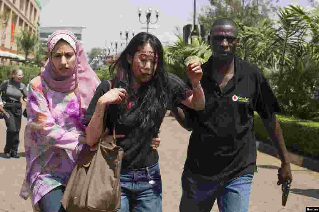 Injured woman is helped out of Westgate Shopping Center where gunmen went on shooting and grenade-throwing spree, Nairobi Sept. 21, 2013.