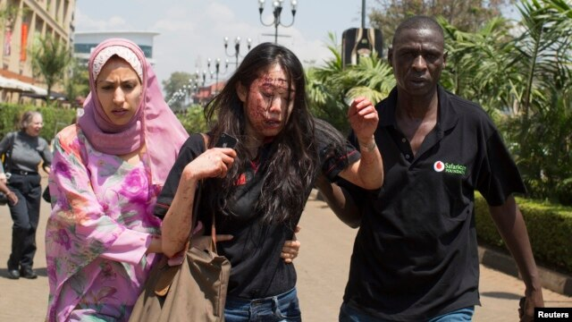 Injured woman is helped out of Westgate Shopping Centre where gunmen went on shooting and grenade-throwing spree, Nairobi Sept. 21, 2013.