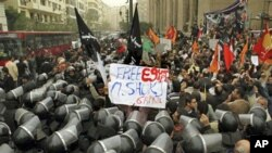 "Egyptian anti-riot soldiers surround protesters, with one displaying a ""Free Egypt"" sign, during a protest against parliamentary elections which they claimed were rigged, Cairo, 12 Dec 2010"