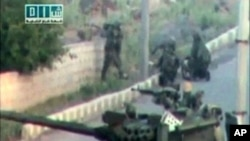 Soldiers take up position near a tank on a street in a location given as Daraa on April 25, 2011, in this still image taken from an amateur video.