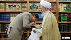 بوسه علی جنتی بر دست مکارم شیرازی. او چندین بار با مراجع تقلید دیدار کرد