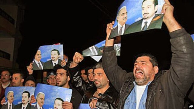 Angry Sunni protesters react as they hold posters showing the slain former prime minister Rafik Hariri, and his son Saad Hariri, who they support, in the southern port city of Sidon, Lebanon, 24 Jan 2011