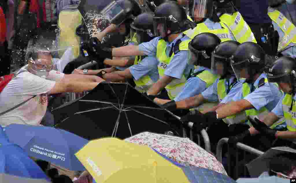 Riot police use pepper spray against protesters outside the government headquarters in Hong Kong.
