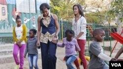 Premyè dam Michelle Obama ak pitit li Sasha ak Malia, k ap mache ak timoun nan zon nan pandan yon vizit nan yon sant kominotè Emthonjeni ki nan Johannesburg (AP Photo/Charles Dharapak, Pool)