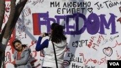 """Anak muda Mesir berfoto di depan tembok yang dipenuhi grafiti (2/13). Salah satu bertuliskan """"Kemerdekaan."""" Era baru di Mesir, menurut pengusaha Indonesia, juga akan menguntungkan hubungan dagang kedua negara."""