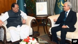 In this photo released by the Pakistan Press Information Department, President of Pakistan Mamnoon Hussain, left, talks with new Care Taker Prime Minister Nasir-ul-Mulk in Islamabad, June 1, 2018.