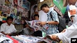 Cư dân mua báo tại một cửa hàng bên đường tại Rangoon, Miến Điện.