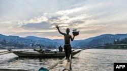 Izabayo, 13 ans, marmites d'une main, débarque d'un bateau de pêche en se balançant sur un pont en tronc d'arbre sur les eaux du lac Kivu, 17 juillet 2017.