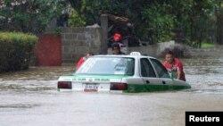 Tres hombres intentan empujar un taxi en una calle anegada por las lluvias de la tormenta Barry en Xalapa, capital del estado de Veracruz, en México.