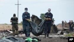 Nhân viên cấp cứu Ukraina khiêng túi chứa thi thể nạn nhân ra khỏi địa điểm vụ tai nạn gần làng Hrabove, miền đông Ukraine, ngày 20/7/2014.