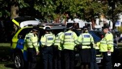런던 경찰이 15일 지하철 테러 사건이 발생한 현장에서 경찰 차량 주변에 모여있다.